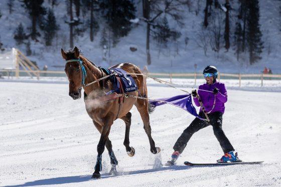 Women skiing behind horse.